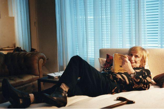 Françoise Sagan sur son lit en train de lire