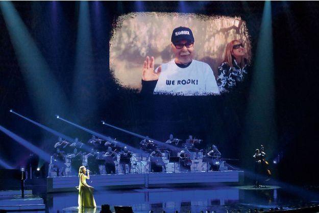 """Sur la scène du Colosseum, Céline Dion interprète la chanson """"The First Time I Ever Saw Your Face"""" devant la photo de René."""