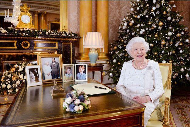 La reine Elizabeth II pose dans son bureau, où se trouvent deux portraits de son époux et elle, et deux photos des petits George et Charlotte.