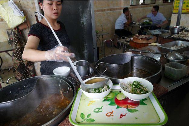 Une femme prépare une soupe de nouilles à Ho Chi Minh Ville, Vietnam.