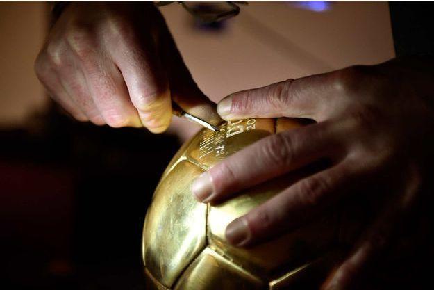 Le ballon d'or entre les mains du graveur.