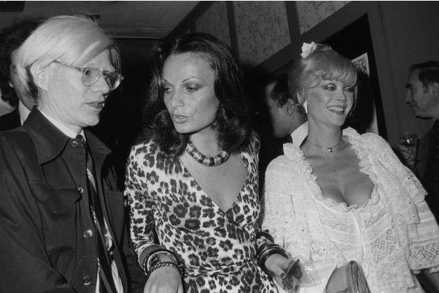 Diane von Furstenberg portant une de ses fameuses robes portefeuilles aux côtés d'Andy Warhol et de l'actrice Monique Van Vooren en 1974.