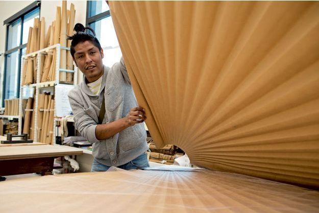 Dans l'atelier Lognon, Raphaël manie le « métier », un moule en carton, pour réaliser un plissage.