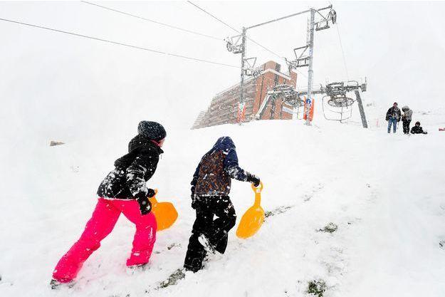 Des enfants font de la luge à La Mongie dans les Pyrénées.