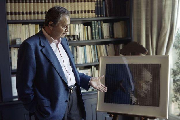 Roger Hanin, chez lui à Paris, devant un portrait de son beau-frère
