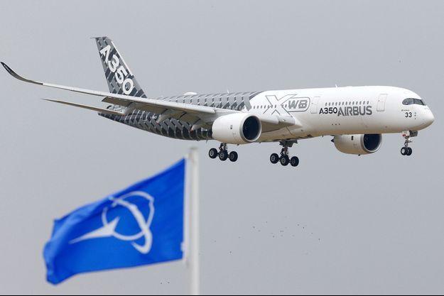 Un Airbus vole devant un drapeau Boeing (image d'illustration).