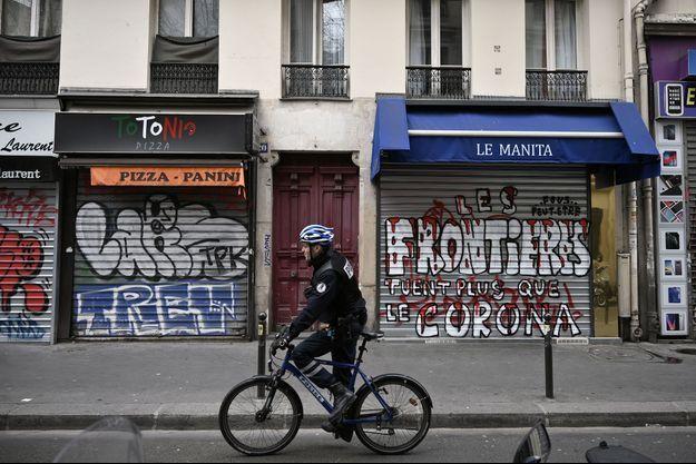 Un policier devant des commerces fermés, près de la Gare du Nord à Paris, le 17 mars.