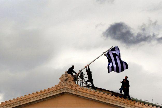 Le 18 avril 2012, à Athènes : des employés du Parlement grec hissent un nouveau drapeau après que le précédent a été déchiré.