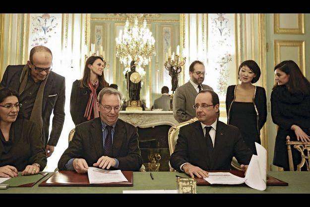 Le 1er février 2013, l'accord est signé par Eric Schmidt et François Hollande. A leur dr. : Nathalie Collin. Au second plan, de g. à dr., David Kessler, conseiller à l'Elysée, la ministre de la Culture, Aurélie Filippetti, Marc Schwartz, le médiateur, Fleur Pellerin, ministre déléguée à l'Economie numérique.