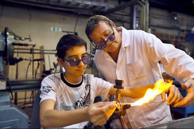 Un employé accompagne un apprenti dans une verrerie à Jointville-le-Pont, en 2012.