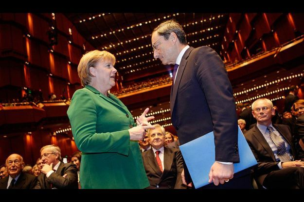 La chancelière allemande Angela Merkel et l'Italien Mario Draghi, le 19 octobre 2011 à Francfort, lors de la cérémonie d'adieu de Jean-Claude Trichet (au centre), son prédécesseur à la tête de la Banque centrale européenne.