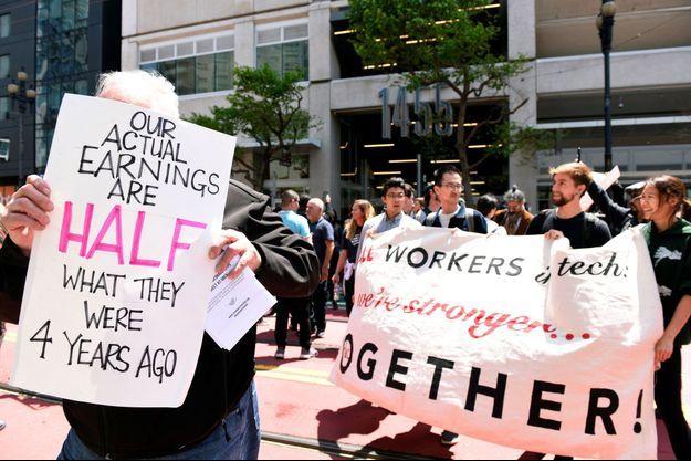 """Manifestation de chauffeurs Uber à San Francisco, en mai. Sur la pancarte de gauche : """"Nos revenus réels ne sont que la moitié de ce qu'ils étaient il y a quatre ans""""."""