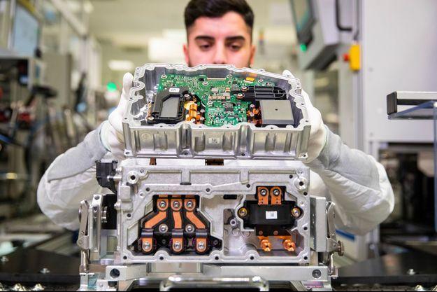 À l'usine Continental de Nuremberg, en Allemagne, un employé assemble un bloc d'alimentation de véhicule électrique.