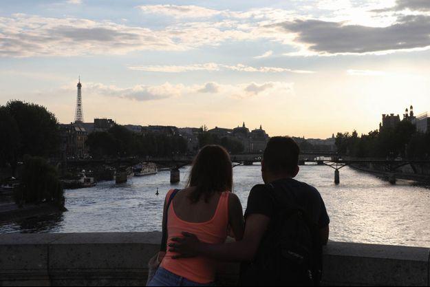 Un couple de touristes regarde le coucher de soleil sur la Seine, avec la Tour Eiffel en fond.