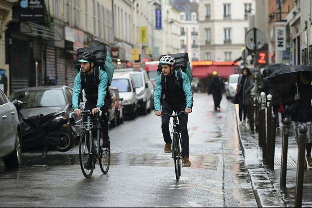 """Deux livreurs Deliveroo à Paris. Les nouveaux services de livraison font appel aux auto-entrepreneurs, un statut que Valérie Segond décrit comme """"la figure héroïque du travail low-cost""""."""