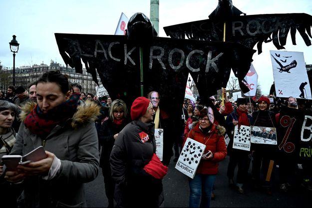Des manifestants dénoncent le rôle de BlackRock place de la Bastille à Paris, le 17 décembre.