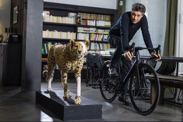 Chez lui, à Paris, sur un vélo fabriqué par sa société Heroïn. A sa droite, un des « Accidents de chasse » du plasticien Pascal Bernier, pour alerter sur la fragilité de l'environnement