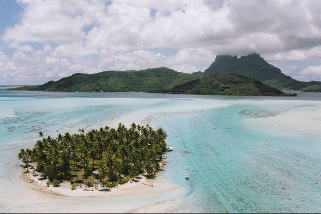 Vue du Motu Haapiti, ilot de corail sur la couronne récifale, au large de Bora Bora. Au loin, le volcan Otemanu.