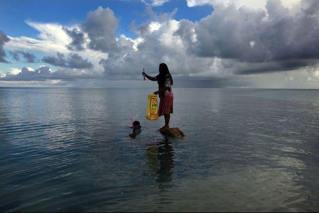 Un couple de pêcheurs de l'atoll de Kiribati, dans le Pacifique, menacé de disparition par la montée du niveau de la mer.