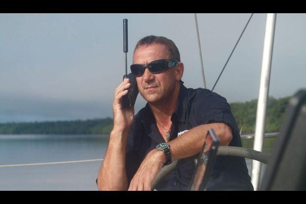 """Patrick Deixonne, chef de l'expédition """"7ème continent"""", essaie un téléphone satellite à Cayenne en Guyane où il réside."""