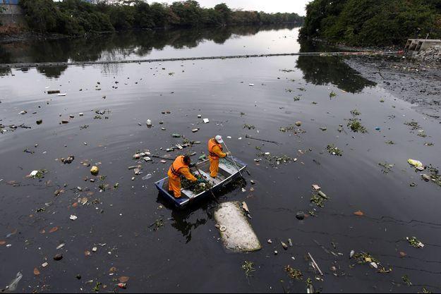 Des travailleurs tentent de ramasser les déchets présents dans la baie de Guanabara
