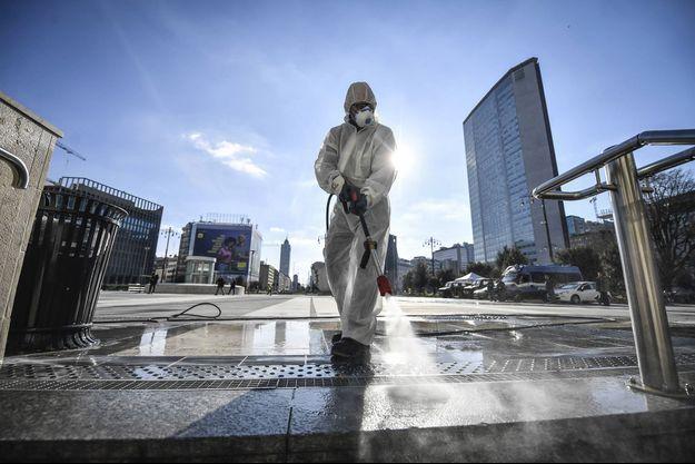 Un agent désinfecte le sol de la gare de Milan, en Italie.