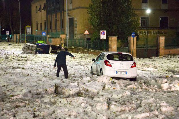 Un homme tente de marcher entre les plaques de glace, formées par une pluie de grêle qui s'est abattue sur Rome dimanche soir.