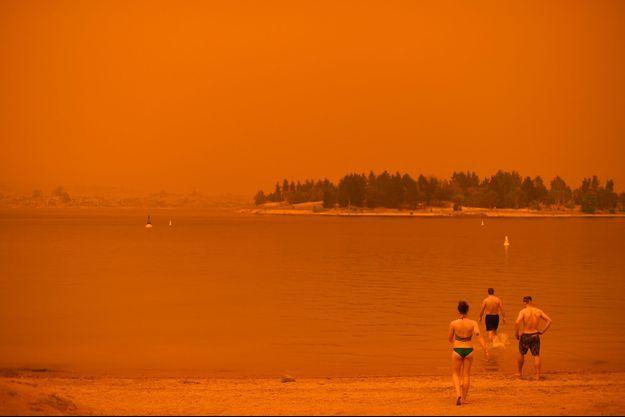 En Nouvelle-Galles du Sud, des habitants se baignent dans le lac Jindabyne, samedi, alors que les incendies ont coloré le ciel en rouge.