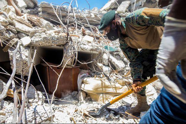 Un soldat nettoie les débris du séisme survenu en Haïti la semaine dernière.