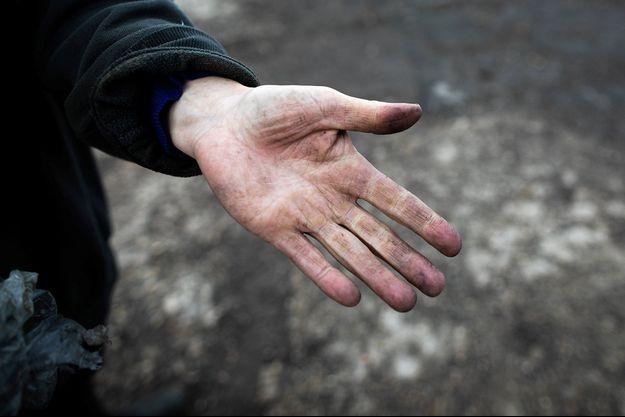 Un agriculteur montre sa main qui porte des traces de suie, près de Rouen.