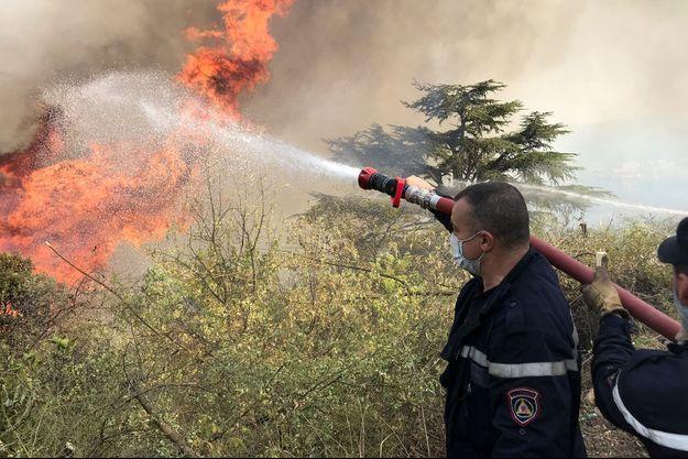 Des pompiers tentent d'éteindre les flammes d'un incendie de forêt dans le village de Tala N'tazert en Kabylie, Algérie, le 13 août 2021