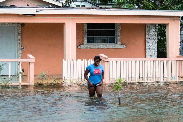 Une femme les jambes dans l'eau à Nassau, aux Bahamas, après le passage de Dorian.