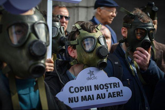 """Manifestation contre la pollution devant le ministère de l'environnement à Bucharest, en Roumanie, le 4 mars 2019. Sur la pancarte : """"Nos enfants ne respirent plus d'air""""."""