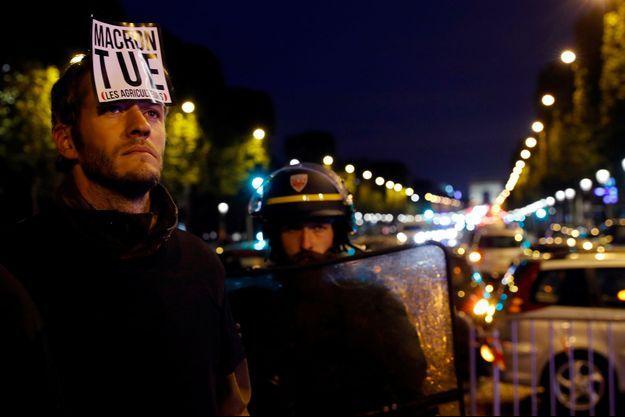 Un agriculteur manifeste sur les Champs Elysées pour contester la politique d'Emmanuel Macron en matière d'agriculture.