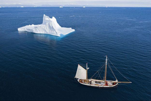 Un voilier à côté d'un iceberg au Groenland.
