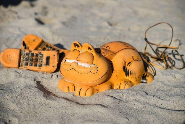 Un téléphone Garfield ensablé sur une plage bretonne.