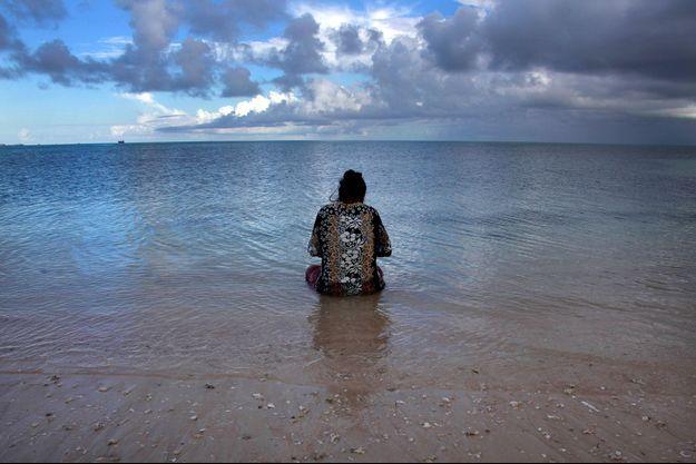 Une femme contemple son mari qui pèche au large des îles Kiribati (Pacifique central). Des atolls dangereusement menacés par la montée des eaux liée au réchauffement planétaire.