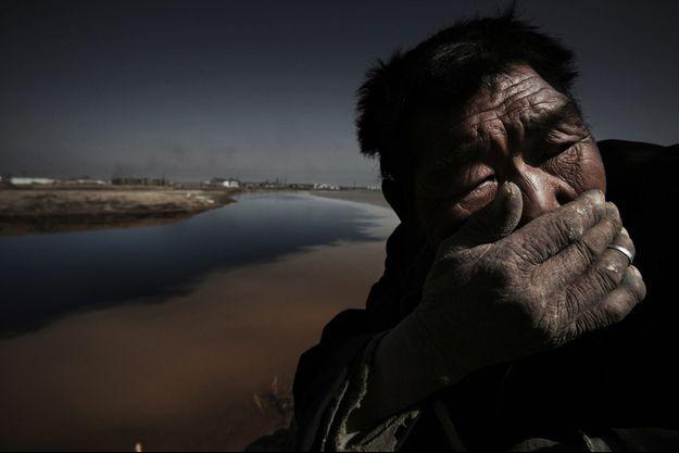 Un berger sur les rives polluées du Fleuve Jaune près de la ville industrielle de Shizuishan