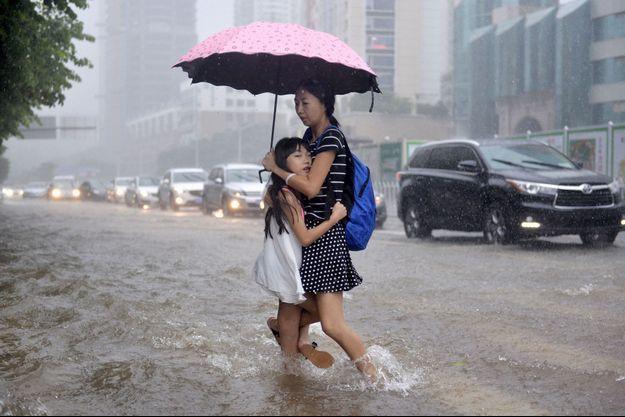 Une femme et son enfant pendant une inondation en Chine, dans la ville de Shenzhen.