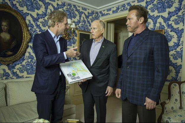 """Olivier Royant, directeur de la rédaction de Paris Match avec Jerry Brown et Arnold Schwarzenegger. Entre ses mains, """"Ma terre en photos"""", l'album de Paris Match pour notre planète."""