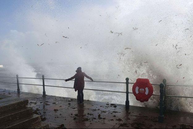 Une femme se tient devant la mer à Penzanze, en Angleterre.