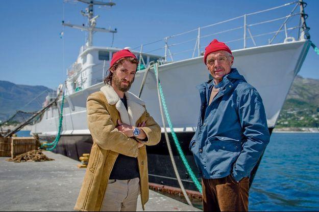 Pierre Niney, qui joue Philippe, le fils cadet de Jacques-Yves Cousteau, et Lambert Wilson, le 27 octobre, dans le port de Hout Bay, en Afrique du Sud. Derrière eux, un dragueur de mines, la « Calypso » du film.
