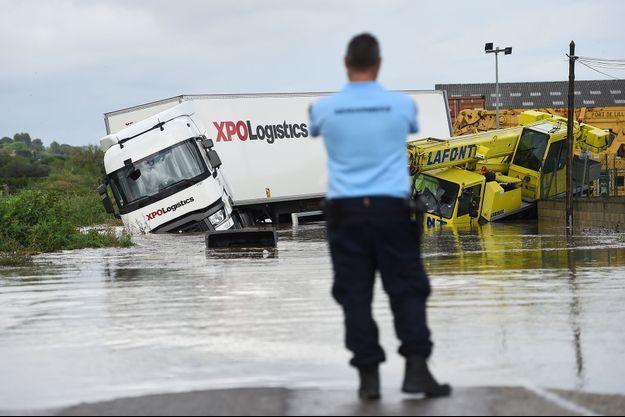 Un officier de gendarmerie français regarde deux camions bloqués sur une route inondée à Codognan, dans le département du Gard, suite aux fortes pluies.