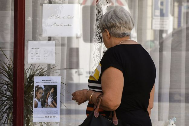 Une femme devant l'avis de recherche pour Maëlys à Pont-de-Beauvoisin. (image d'illustration)