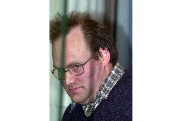 Jean-Louis Jourdain, ancien ferrailleur, regarde la salle d'audience à travers la vitre blindée de son box le 18 mars 2002 au palais de justice de Douai.