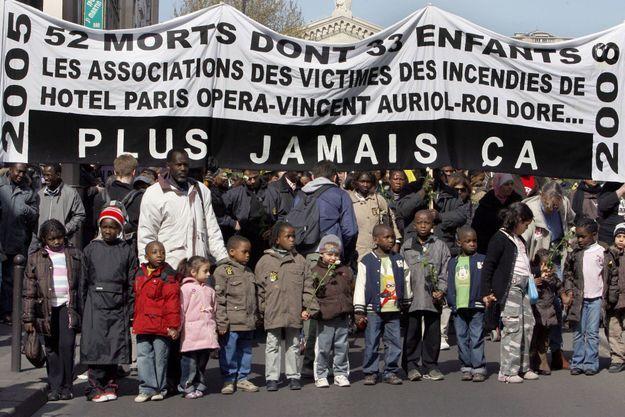 Des proches des victimes de l'incendie de l'hôtel Paris Opéra survenu le 15 avril 2005 et de drames similaires survenus la même année, défilent dans les rues de Paris le 12 avril 2008.