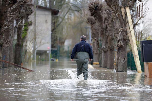 Un homme marche dans les rues inondées, dans l'Essonne (image d'illustration).