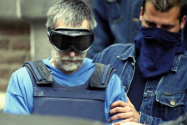 Les yeux masqués, l'assassin quitte le commissariat de Dinant, après une confrontation avec les enquêteurs. Juillet 2004.