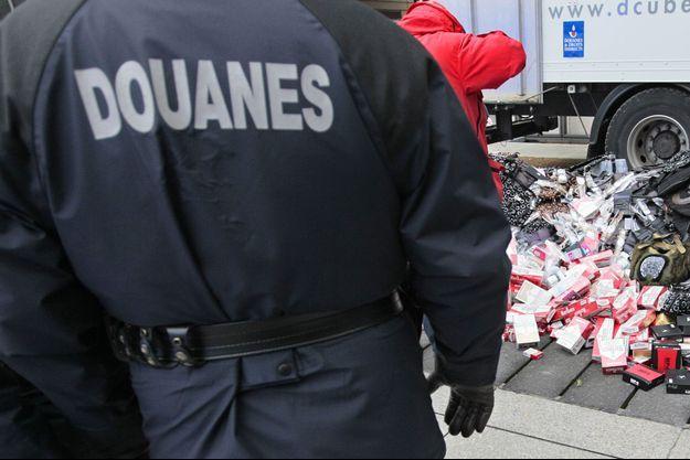 Un gendarme regarde, le 27 janvier 2011, Paris, des articles de contrefaçon avant leurs destructions.