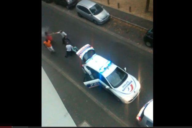 Capture d'écran à 1:23 de la vidéo montrant un policier utilisant une bombe lacrymogène.